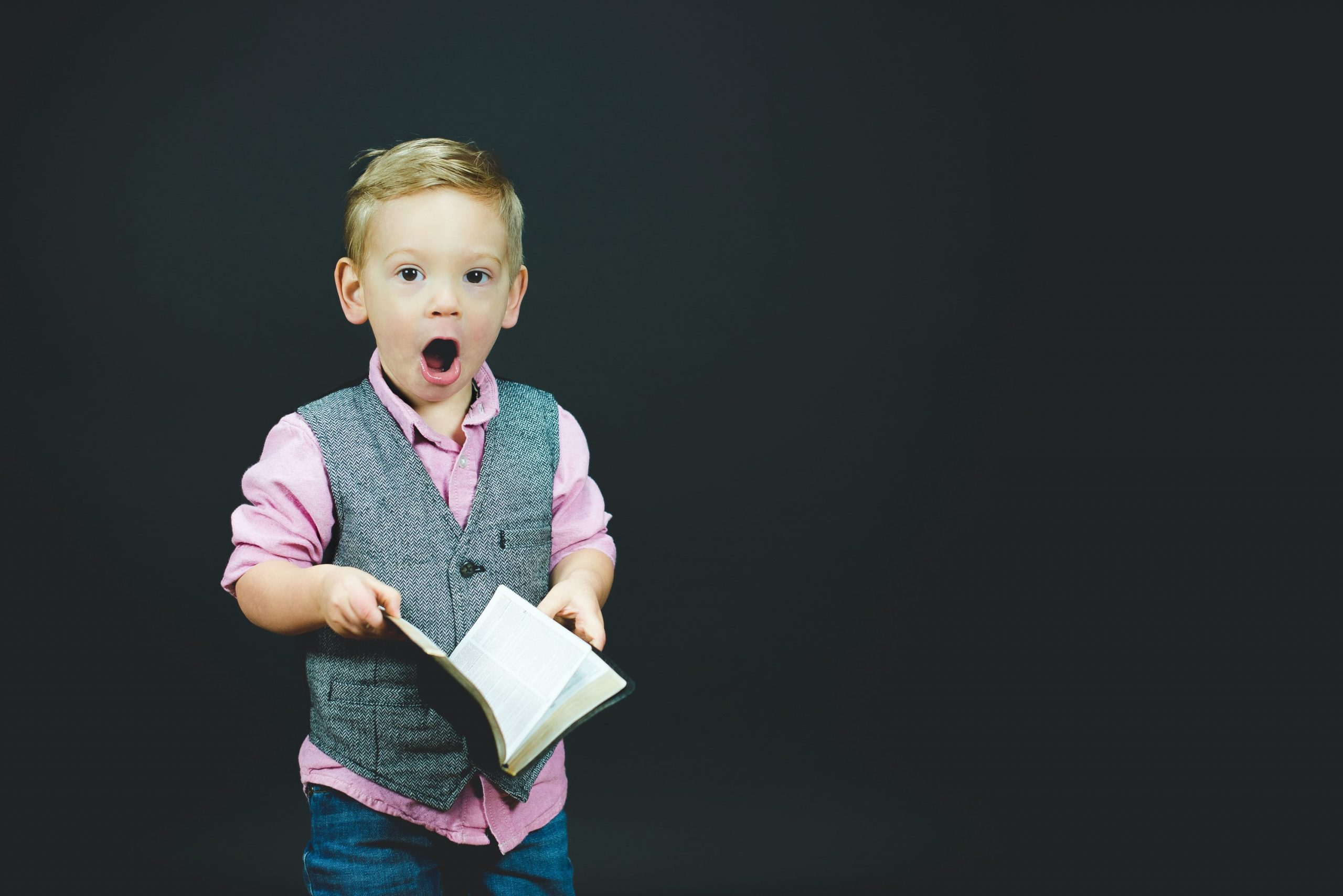 Photo by Ben White on Unsplash. Boy opening book looking surprised
