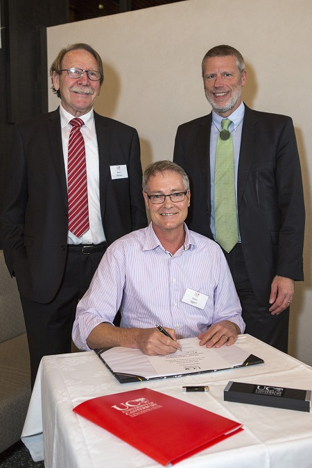 Vice Chancellor Dr Rod Carr signing agreement with Pells Sullivan Meynink. Pictured: Mark Eggers Director PSM (sitting), Barry Ramsay Chair UC Foundation and Dr Rod Carr.
