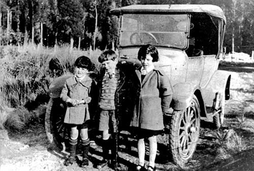 MB 1065, A.C. Graham photographs, Reference code 20765, Jim, Mick and Mary Sullivan with family's first car, c. 1920, Photographer unknown, Macmillan Brown Library, University of Canterbury